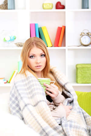 Attractive young woman sitting on sofa, holding cup with hot drink, on home interior background Stock Photo - 17761977