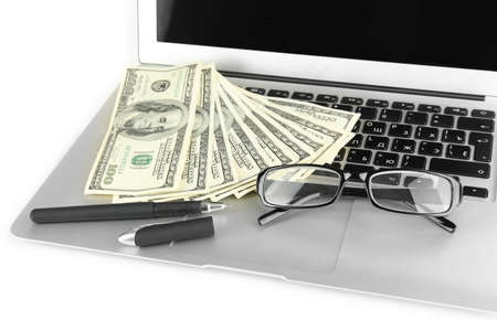 Money with glasses and pen on laptop isolated on white photo