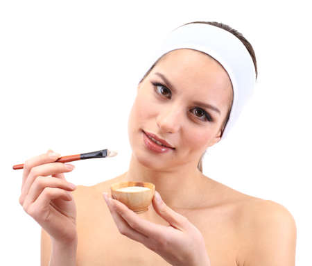 Young woman applying clay facial mask, isolated on white photo