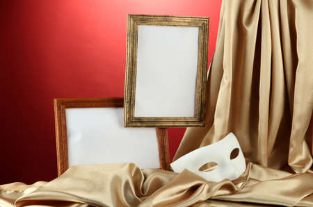 White mask, empty frames and golden silk fabric, on red background photo