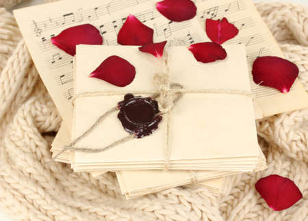 Stacks of old letters and music sheets with dried rose petals on soft scarf photo