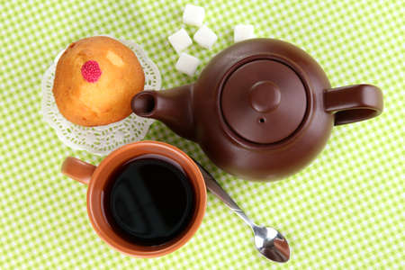 Top view of cup of tea and teapot on green tablecloths photo