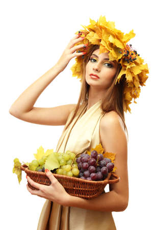 beautiful young woman with yellow autumn wreath and grapes in basket, isolated on white photo