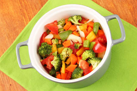 Vegetable stew in gray pot on color napkin on wooden background photo