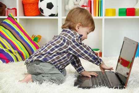 cute little boy and notebook in room