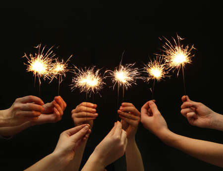beautiful sparklers in hands on black background  photo