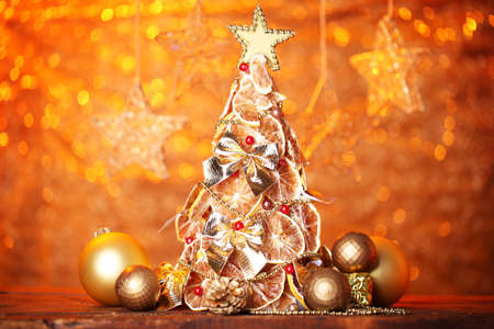 beautiful christmas tree of dry lemons with decor, on orange background photo
