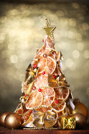 beautiful christmas tree of dry lemons with decor, on  shine background photo