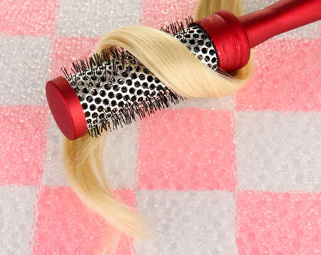 comb brush with hair on pink  tile wall background photo