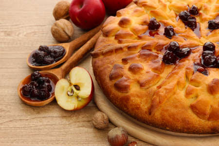 tasty homemade pie with jam and apples, on wooden table photo