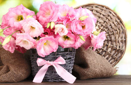 bouquet of eustoma flowers in  wicker vase, on wooden table, on green background photo