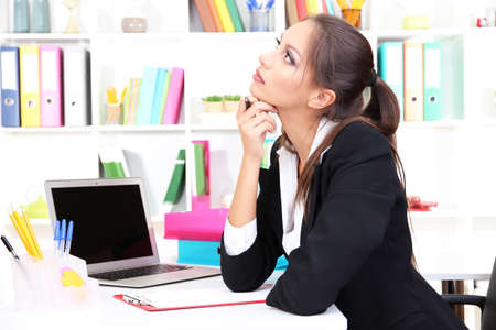 thoughtful woman: Thoughtful business woman with documents and notebook in office