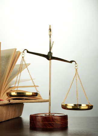 judicature: Gold scales of justice and books on grey background