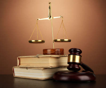 Golden scales of justice, gavel and books on brown background Stock Photo - 17676230