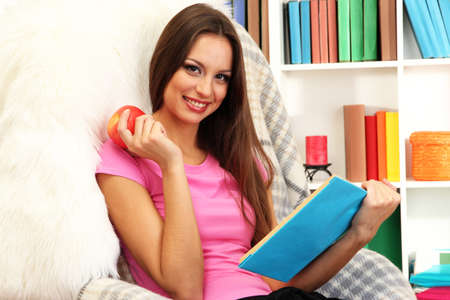 Portrait of female eating apple and reading book at home photo