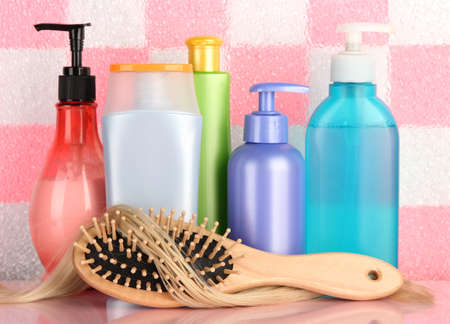 comb brush with hair and cosmetic bottles in bathroom photo
