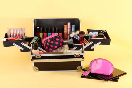 open case with cosmetics on yellow background photo