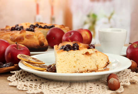 slice of tasty homemade pie with jam and apples and cup of coffee, on wooden table photo