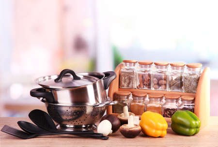 cooking utensils: composition of kitchen tools,spices and vegetables on table in kitchen