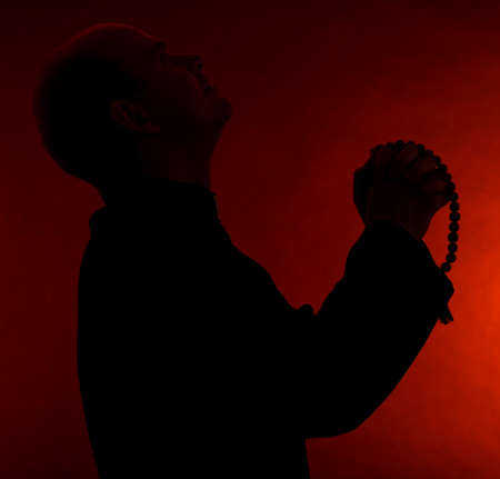 Young pastor with wooden rosary, on dark red background
