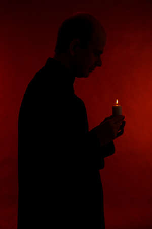 Portrait of young Pastor holding candle in his hand, isolated on black photo