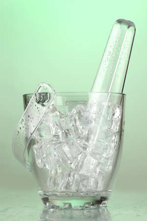 Glass ice bucket on light green background photo
