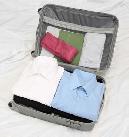 Open grey suitcase with clothing on bed Stock Photo - 17673871