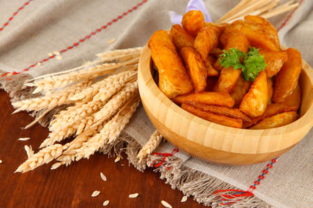 nutritiously: Appetizing village potatoes in bowl on wooden table close-up