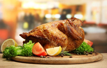 Whole roasted chicken with vegetables on plate, on wooden table in cafe photo