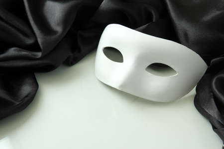 White mask and black silk fabric, isolated on white photo
