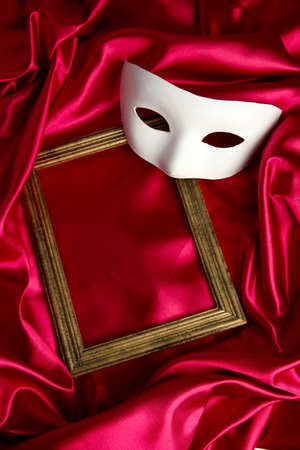White mask and empty frame on red silk fabric Stock Photo - 17684114