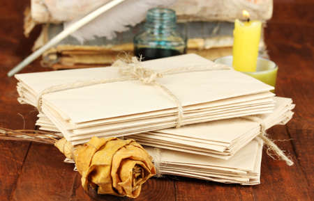 Stacks of old letters on wooden table photo