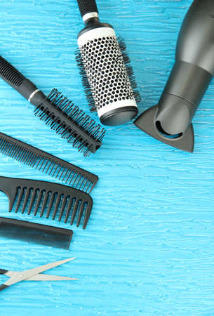 hair black color: Comb brushes, hairdryer and cutting shears,on color background