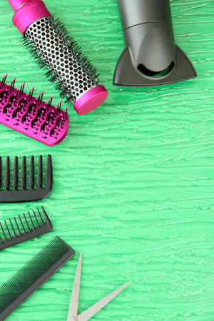 Comb brushes, hairdryer and cutting shears,on color background photo