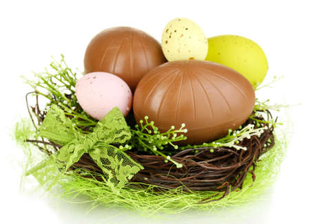 elliptic: Composition of Easter and chocolate eggs in nest isolated on white
