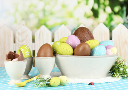 Composition of Easter and chocolate eggs on natural background photo