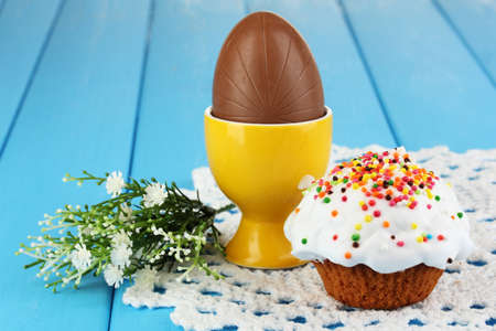 Composition of Easter and chocolate eggs on wooden table close-up photo