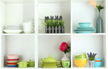 Beautiful white shelves with tableware and decor  photo