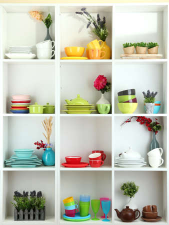 Beautiful white shelves with tableware and decor  Stock Photo