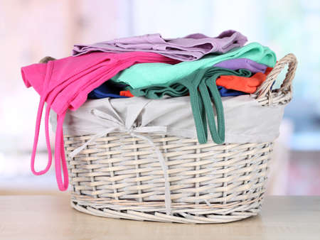 Clothes in wooden basket on table in room Stock Photo - 17663423