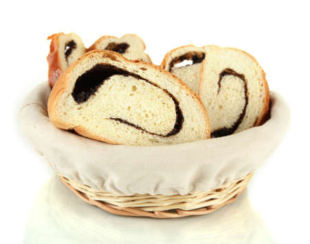 Loaf with poppy seeds in wicker basket, isolated on white  photo