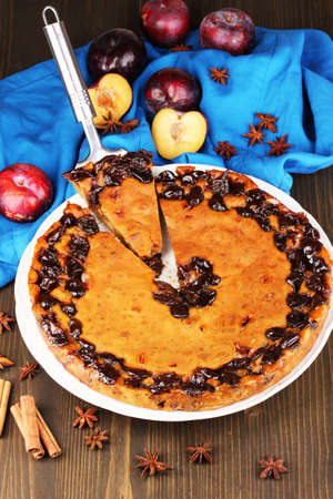 Tasty pie on plate with plums on wooden table Stock Photo - 17705076