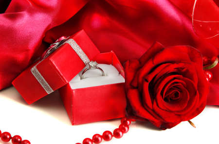 Beautiful box with wedding ring and rose on red silk background photo