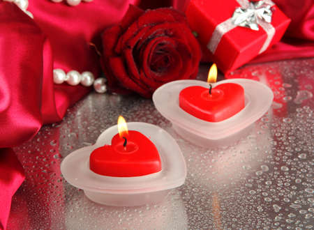 Beautiful candles, rose and red silk on grey wet background photo