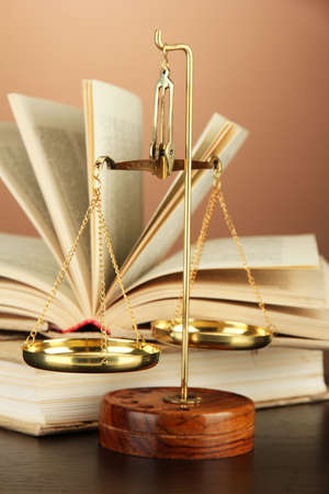 judicature: Gold scales of justice and books on brown background