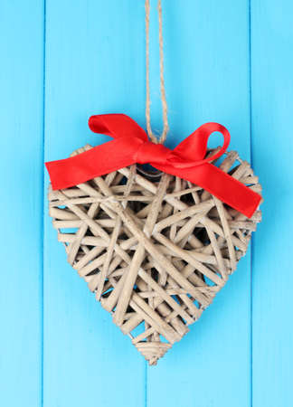 Wicker heart with red bow on wooden background photo