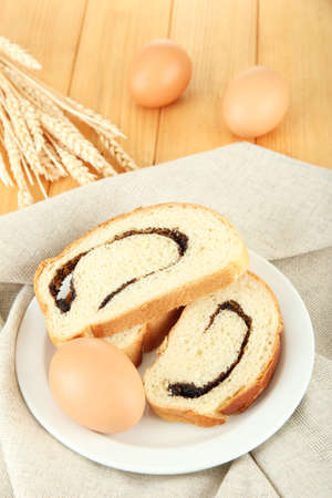 Loaf with poppy seeds on color plate, on wooden background Stock Photo - 17797442