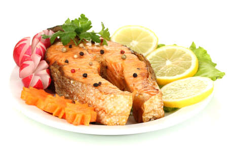 prepared food: Appetizing grilled salmon with lemon and vegetables isolated on white
