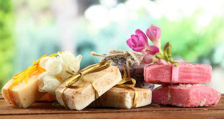 Jabón natural hecho a mano, sobre la mesa de madera, sobre fondo verde Foto de archivo