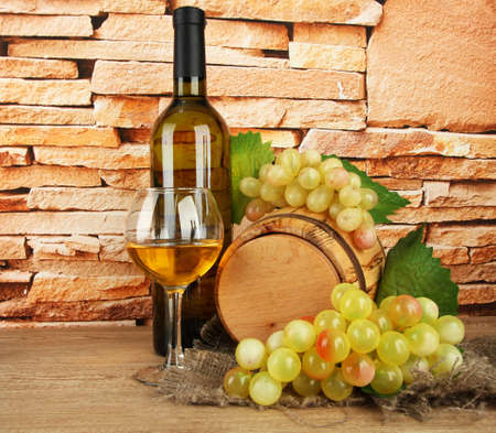 composition of wine and grapes on wooden barrel on table on brick wall background photo